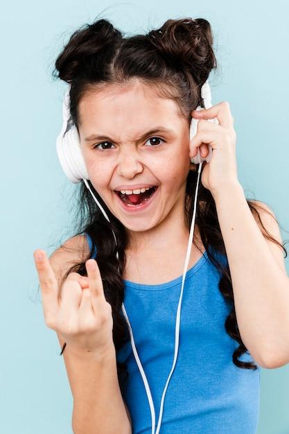 Smiley girl listening rock music at headphones Free Photo