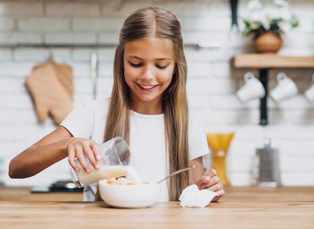 Smiley girl pouring milk in a cereal bowl Free Photo