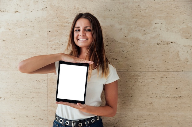 Smiley girl showing tablet with mock-up Free Photo