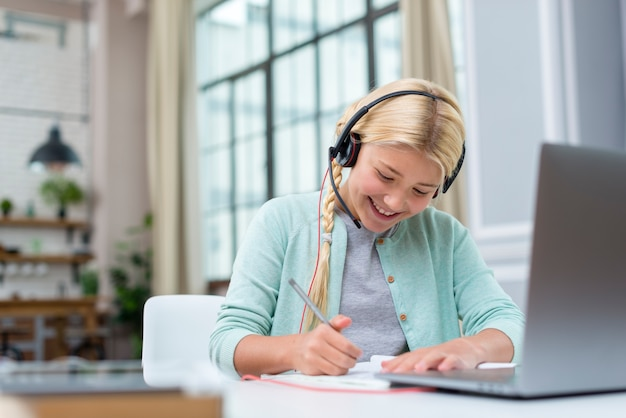 Smiley girl taking notes from online course Premium Photo