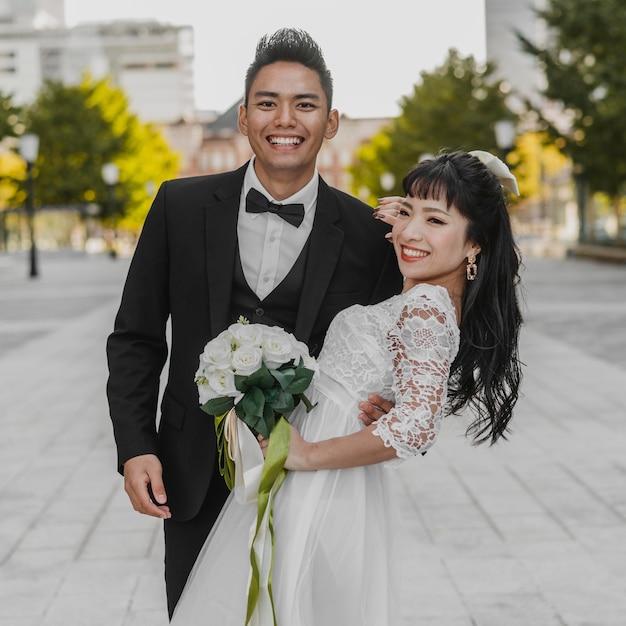 Sposo di smiley che tiene sua moglie in strada Foto Gratuite