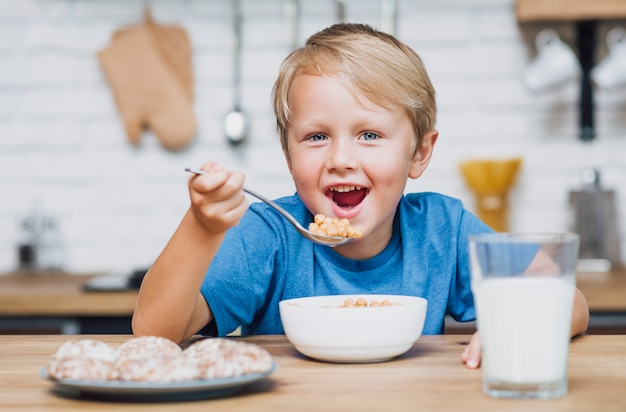 Smiley kid eating cereal Photo | Free Download