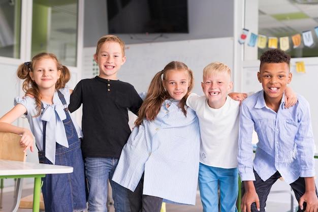 Bambini di smiley che propongono insieme in classe Foto Gratuite