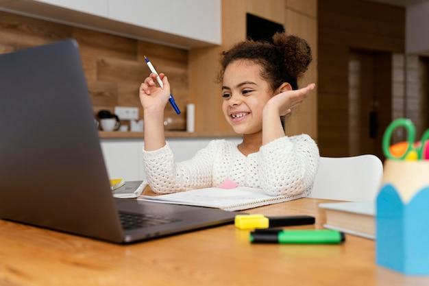 オンライン学校の間に家にいるスマイリーの小さな女の子 無料写真
