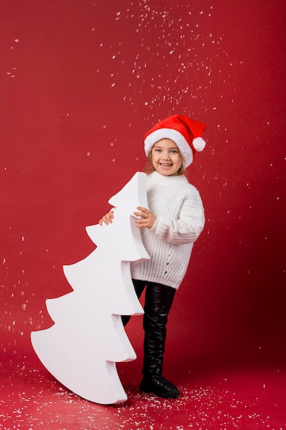 Smiley little girl holding an artificial white tree while snowing Premium Photo