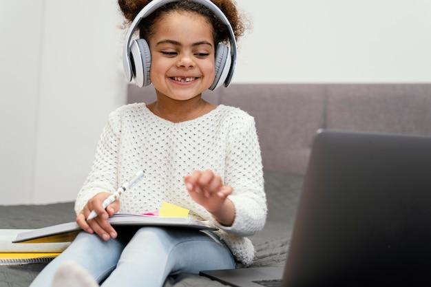 온라인 학교에 노트북을 사용 하여 웃는 어린 소녀 무료 사진