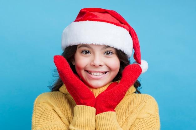 Smiley little girl wearing christmas hat Free Photo