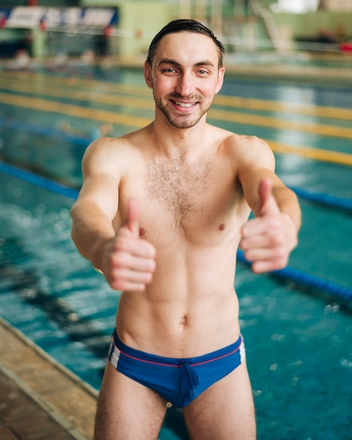 Smiley male swimmer showing ok sign Free Photo
