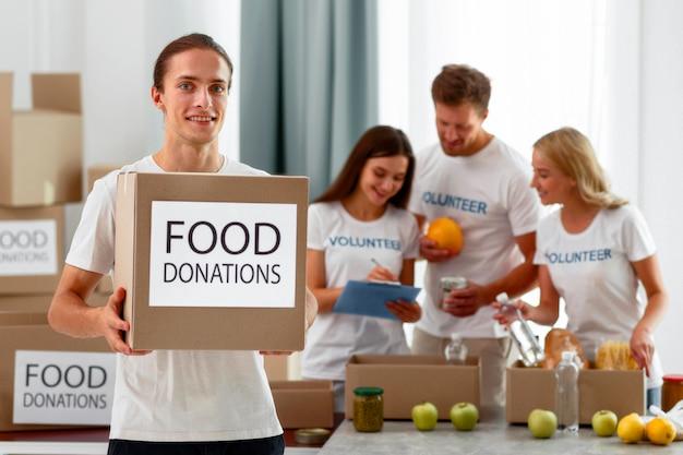 Смайлик-волонтер-мужчина держит коробку с продуктами ко всемирному дню еды Бесплатные Фотографии