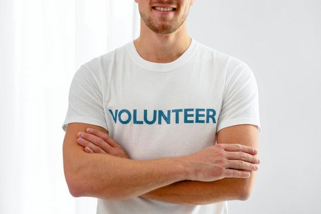 Смайлик-волонтер-мужчина позирует со скрещенными руками Бесплатные Фотографии
