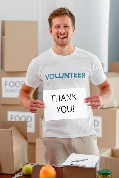 Volontario maschio sorridente che ti ringrazia per aver donato cibo Foto Gratuite