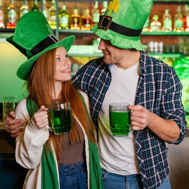 聖を祝うスマイリーの男と女。ドリンクを飲みながらバーでパトリックの日 無料写真