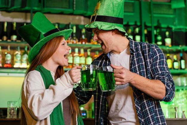 聖を祝うスマイリーの男と女。飲み物とパトリックの日 無料写真