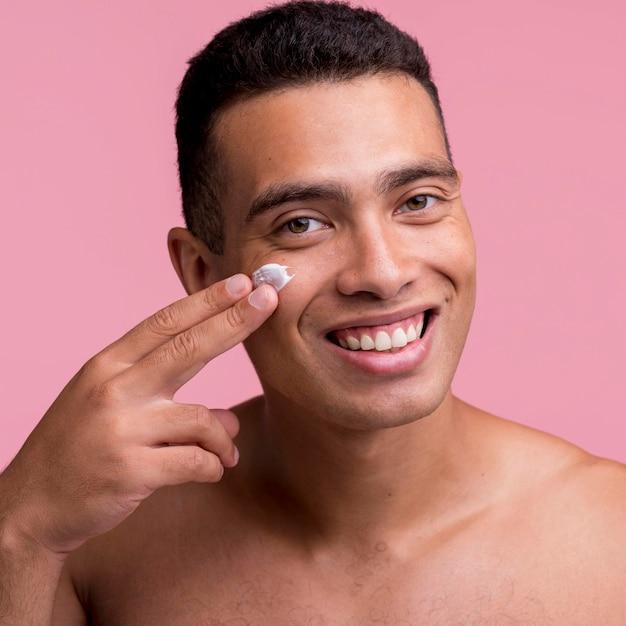 Smiley man applying cream on his face Free Photo