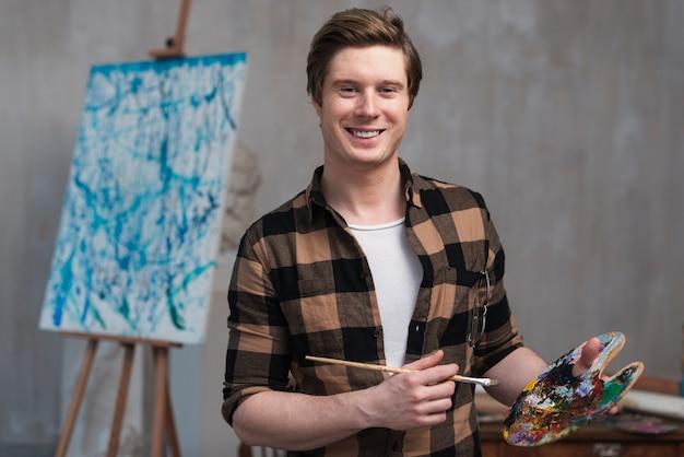Uomo di smiley che mescola colori diversi per la sua pittura Foto Gratuite