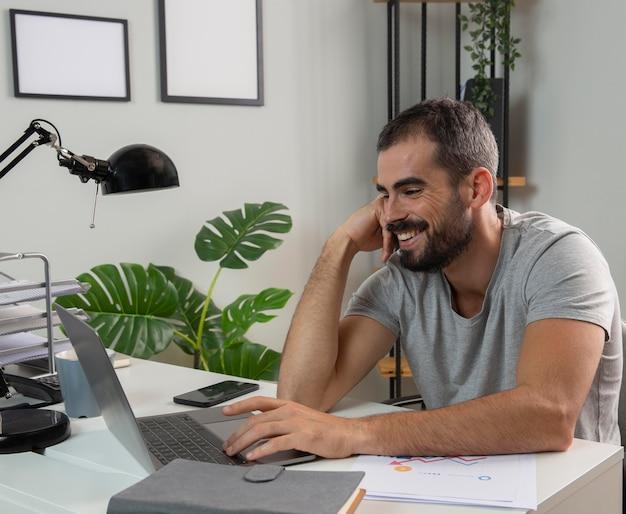 Uomo di smiley che gode del lavoro da casa Foto Gratuite