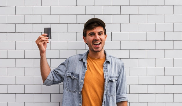 Smiley man holding car on wall background Free Photo