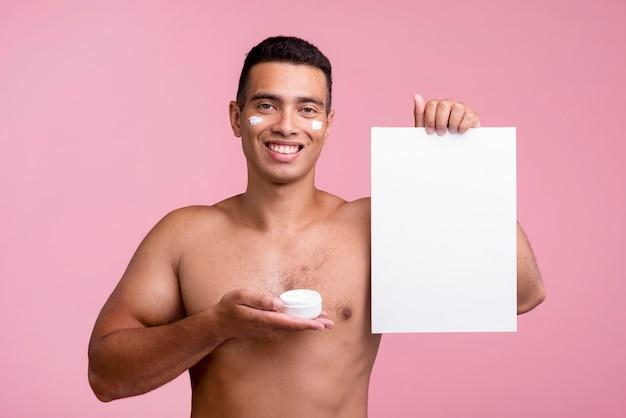 Uomo di smiley che tiene crema per il viso e cartello bianco Foto Gratuite