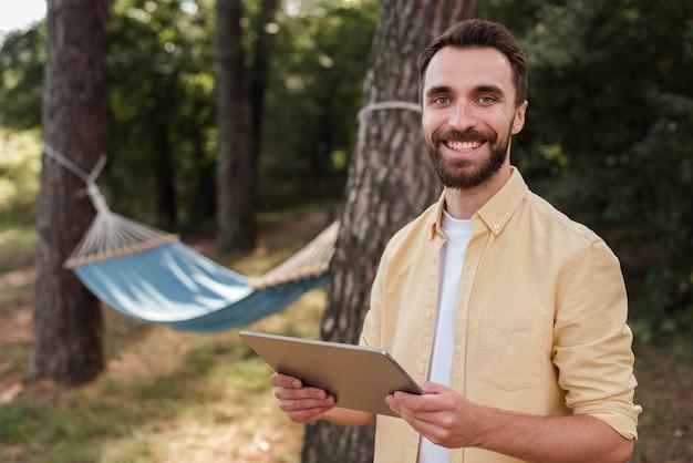 Смайлик мужчина держит планшет во время кемпинга на открытом воздухе Бесплатные Фотографии