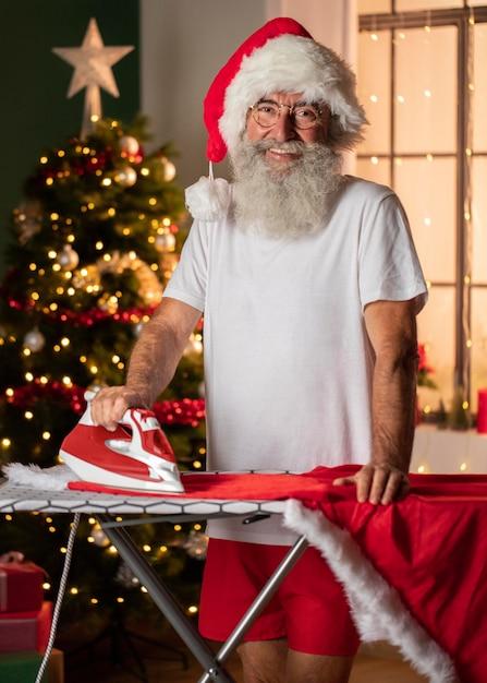 Смайлик в новогодней шапке гладит свой костюм Premium Фотографии