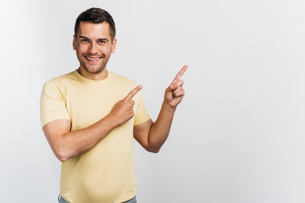 Smiley man pointing in one direction copy space Free Photo