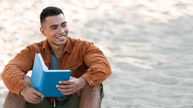 Смайлик человек читает книгу на пляже с копией пространства Бесплатные Фотографии