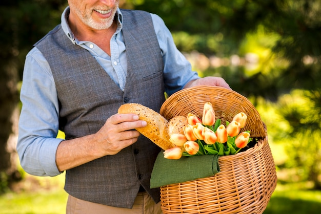 Smiley man taking a baguette from the picnic basket Free Photo