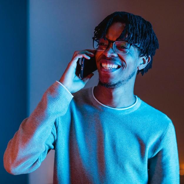 Uomo di smiley utilizzando parlando sullo smartphone Foto Gratuite
