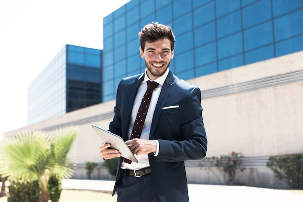 Smiley man with tablet looking at the camera Free Photo