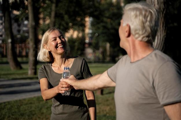 Смайлик зрелая пара пьет воду на открытом воздухе Бесплатные Фотографии