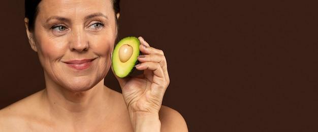 Смайлик зрелая женщина, держащая половину авокадо с копией пространства Бесплатные Фотографии