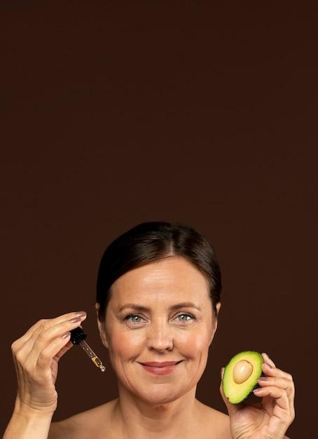 Смайлик зрелая женщина, держащая половину авокадо с сывороткой и копией пространства Бесплатные Фотографии