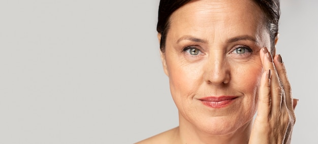 Smiley mature woman with make-up on posing with hand on face and copy space Premium Photo
