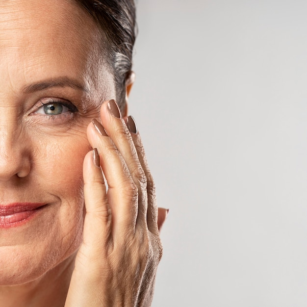 Smiley mature woman with make-up on posing with hand on face Free Photo