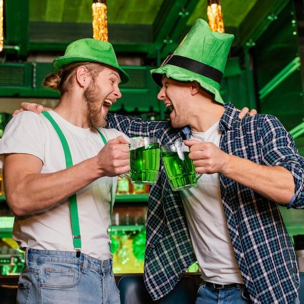 セントを祝うスマイリーの男性。飲み物を飲みながらバーでパトリックの日 無料写真