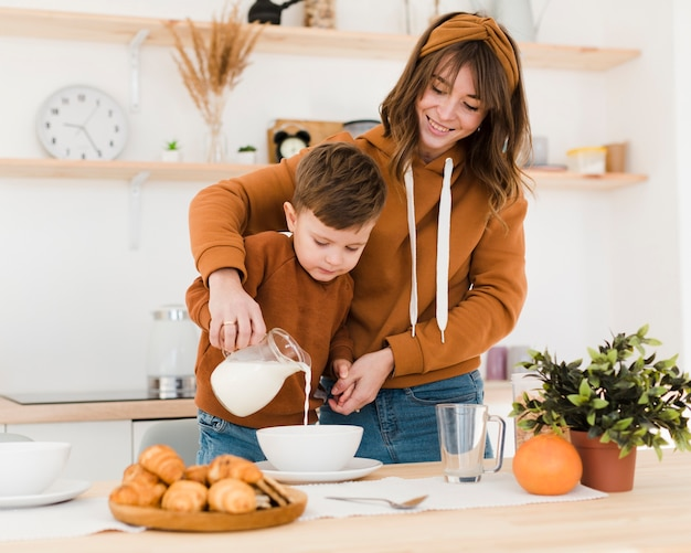 Smiley mom and son in the kitchen Free Photo