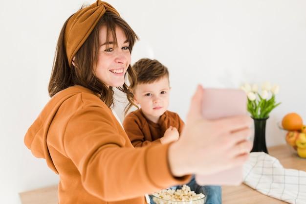 Улыбающаяся мама, делающая селфи Бесплатные Фотографии