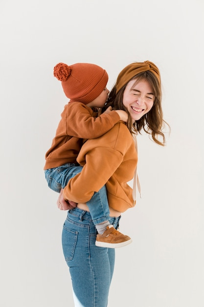 Smiley mom with son on piggy back ride Free Photo