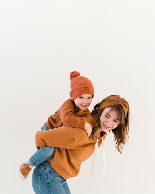 Smiley mom with son in piggy back ride Free Photo
