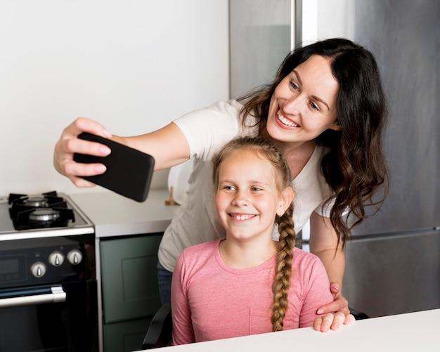Смайлик мама и девушка, принимая селфи Бесплатные Фотографии