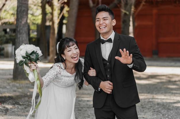 웃는 신혼 부부가 결혼 날을 흔들며 즐겁게 무료 사진