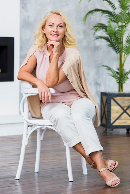 Smiley old lady looking at the camera while sitting on white chair Free Photo