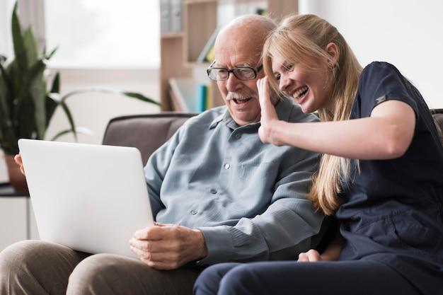 Uomo anziano e infermiera di smiley che hanno una videochiamata sul computer portatile Foto Gratuite