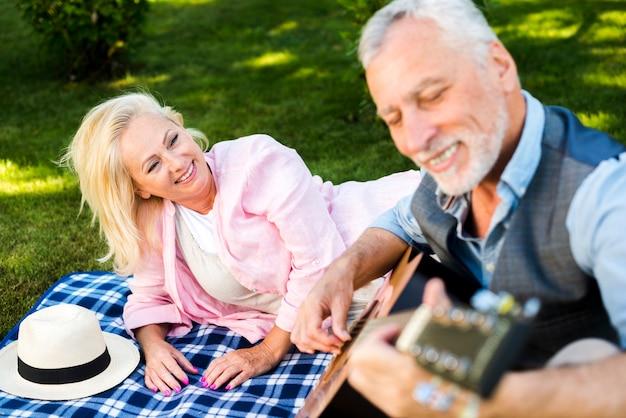 Smiley old man playing guitar at the picnic Free Photo