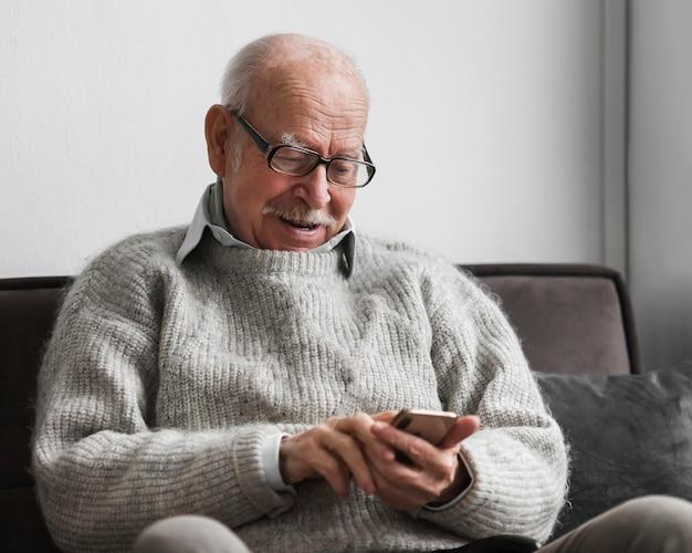 Uomo anziano sorridente che utilizza smartphone in una casa di cura Foto Gratuite