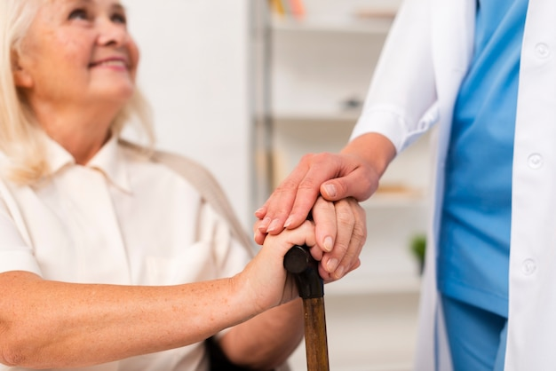 Smiley old woman holding hands with nurse close-up Free Photo