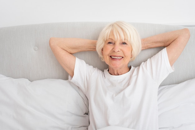 Smiley old woman sitting in the bedroom Free Photo