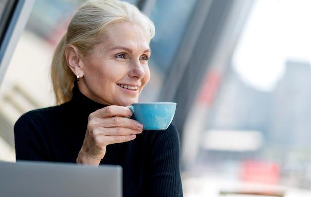 Смайлик пожилой деловой женщины за чашкой кофе на открытом воздухе во время работы Бесплатные Фотографии