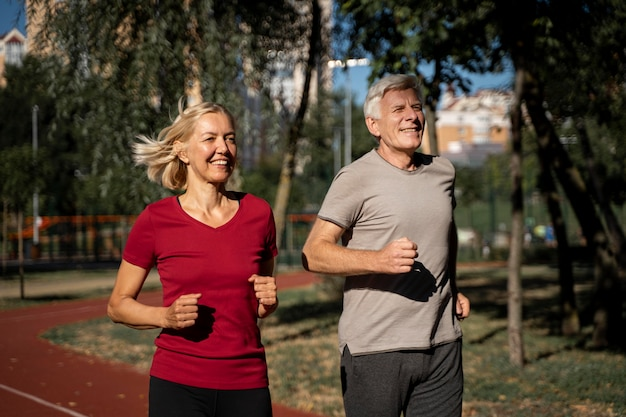 Smiley older couple jogging outdoors Free Photo