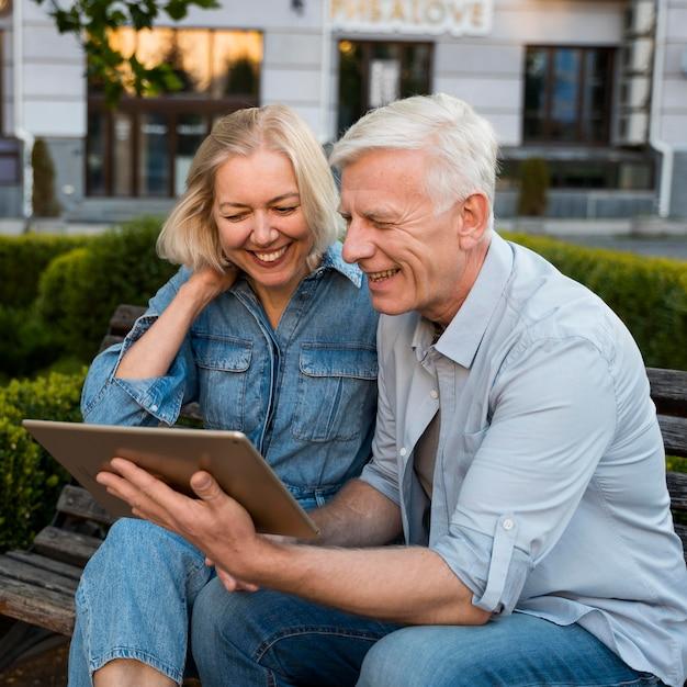 Смайлик пожилая пара смотрит на планшет в городе Бесплатные Фотографии